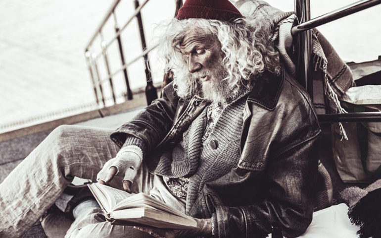 Old dirty loafer reading book that passer by giving him